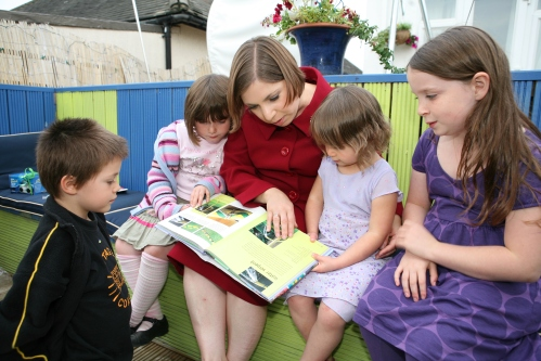 Sarah Teather MP reading a book with pupils